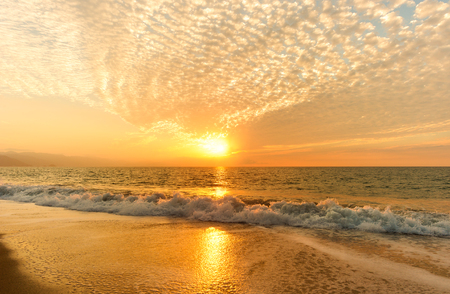 Ocean Sunset is a golden reflection off a gentle wave rolling to shore as the sun sets in the cloud filled sky.
