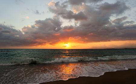 La puesta del sol del océano es una onda de la puesta del sol del océano que rueda a la orilla mientras que el sol se pone en el horizonte del océano.