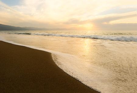 Il tramonto dell'oceano è un'onda di tramonto sull'oceano che scorre a riva quando il sole tramonta sull'orizzonte dell'oceano. Archivio Fotografico - 87636303