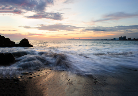 Sunset ocean is a serene scenic seascape on the beach with the bright sun setting on the ocean horizon as water rushes to the shore. Stock Photo