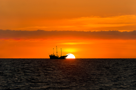 Ship pirate silhouette is a pirate ship sitting at sea watching the ocean sunset silhouetted against the sun..