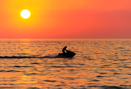 Jetski is a sunset silhouette of a waverunner jetski male riding along the ocean water at sunset. Stock Photo