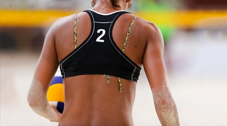 Volleyball beach is a female beach volleyball player getting ready to serve the ball . Stock Photo