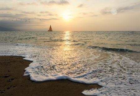 Sunset sailboat is a sailboat sailing along the ocean at sunset. Stock Photo