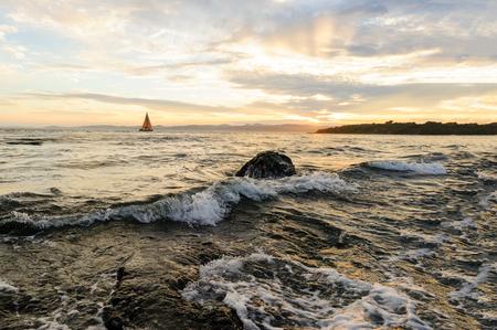 Sailboat sunset is a sailboat sailing along the ocean at sunset.