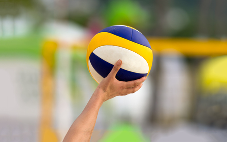 Volleyball is a volleyball player holding up a volleyball getting ready to serve. Stock Photo