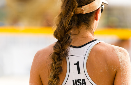 Volleyball beach serving is a female beach volleyball player getting ready to serve the ball. Stock Photo