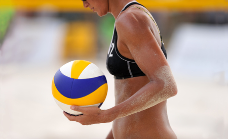 Volleyball beach is a female beach volleyball player getting ready to serve the ball . Фото со стока