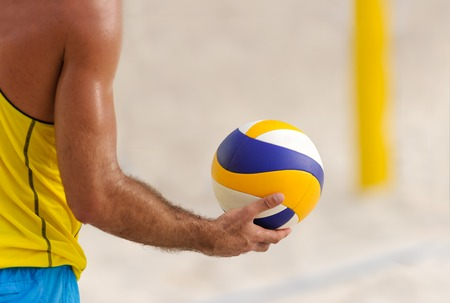 Volleyball is a male volleyball player getting ready to serve the ball. Stock Photo