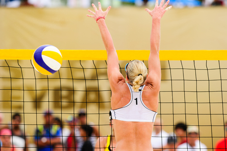 Beach volleyball player is a female beach volleyball player jumping up getting ready to block the ball.