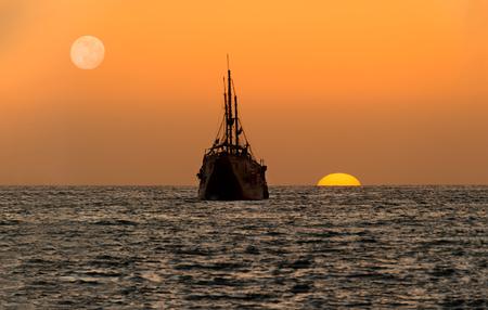 La siluetta della nave del tramonto dell'oceano è una vecchia nave di legno che si siede al mare che guarda il tramonto sull'orizzonte dell'oceano. Archivio Fotografico - 90087909