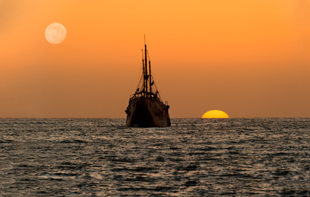 Ocean sunset ship silhouette is an old wooden ship sitting at sea watching the sunset on the ocean horizon.