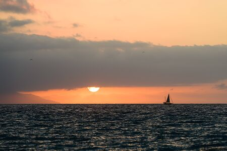 Ocean Sunset Sailboat is a Boat Sailing Along the Ocean While the Sun Sets on the Horizon Фото со стока