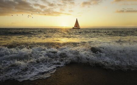 A Sailboat and it's Sail are Back Lit By the Ocean Sun as it Sets on the Horizon Фото со стока - 139263758