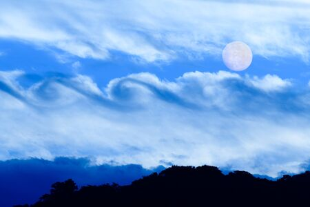 Full Moon is Rising in the Night Sky Over a Surreal Fantasy Like Cloudscape