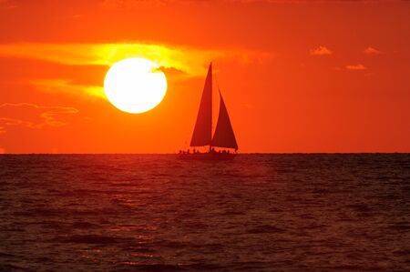 A Sailboat is sailing along the water silhouetted against an orange sunset sky in a peaceful serene nature landscape.