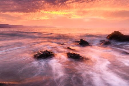 A Long Time Exposure of an Ocean Sunset that Captures the Soft Flow of the Sea Water Rushing to Shore