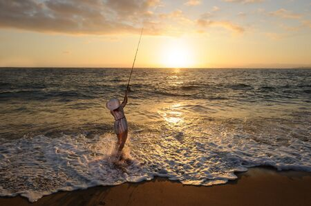 Ocean Fishing Casting is a Woman Cast Fishing on the Beach at Sunset