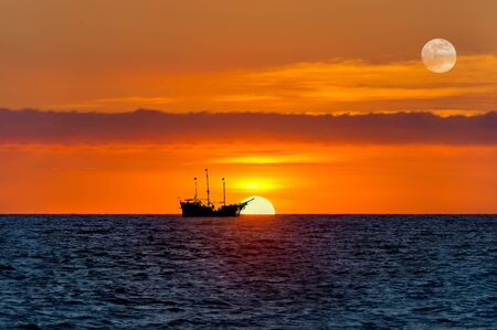 An Old Wooden Ship Sits at sea as the Sun Goes Down on the Ocean Horizon and the Moon Rises in the Sky Stockfoto