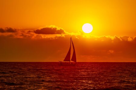 A Sailboat Sails Along the Ocean as the Sun Sets Above the Clouds on the Horizon