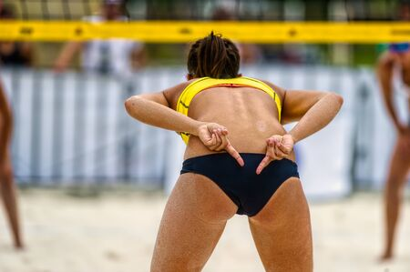 A Female Beach Volleyball Player os Sending Signals to her Teammate
