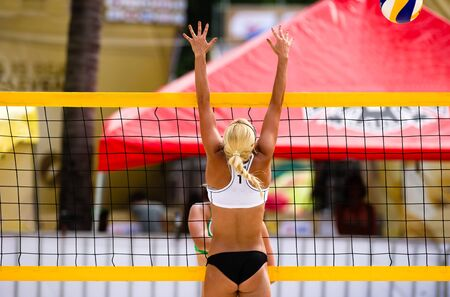 A Female Beach Volleyball Player is Jumping at the Net to Block the Ball Imagens