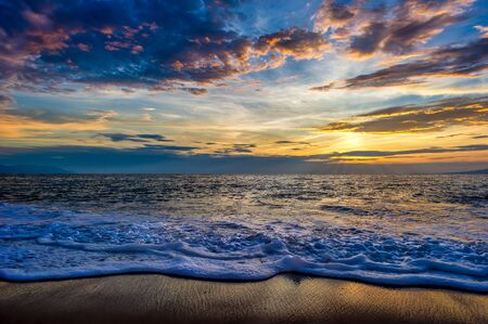 A Colorful Ocean Sunset Landscape as a Wave Comes to the Beach Shore Imagens