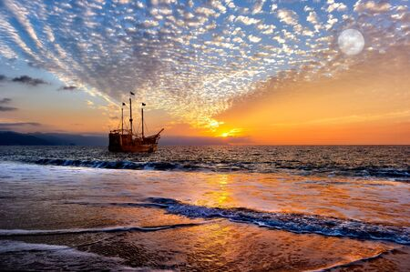 An Old Wooden Pirate Ship Sits on the Ocean at Sunset as the Full Moon rises in the Sky