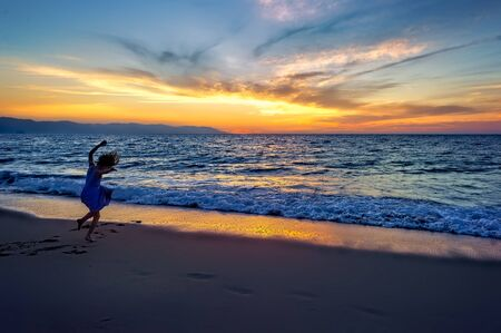 A Girl is at the Beach at Sunset Jumping with Excitement as the Sun Sets on the Ocean