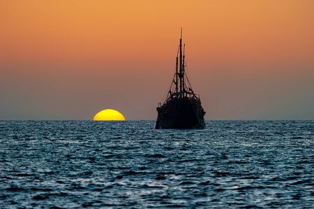 An Old Wooden Pirate Ship Sits on the Ocean at Sunset Silhouette Against the Sunset Sky Imagens