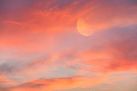 The Moon is Rising in the Sky Surrounded by Vivid Colorful Clouds