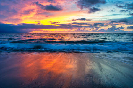 A Colorful Ocean Sunset Sky as a Gentle Wave Rolls to Shore Stockfoto