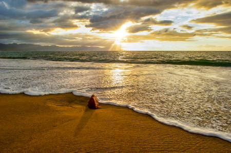 A Gentle Wave Rolls to the Ocean Shore as Sun Rays Burst Through the Clouds