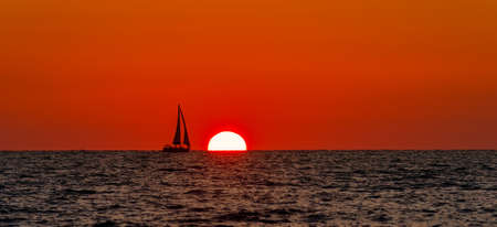 A Sailboat is Sailing Along With an Ocean Sunset 写真素材