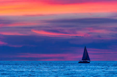 A Sailboat is Sailing Along the Ocean Water at Night 写真素材
