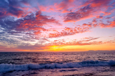 A Colorful Ocean Sunset Sky as a Gentle Wave Rolls to Shore 写真素材