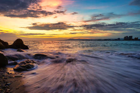 A Colorful Sunset on the Ocean With a Wave Rushing to Shore and Buildings in the Background 写真素材