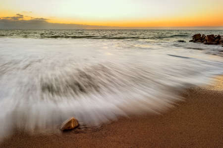 A Gentle Wave Rolls Over a Beach Rock as the Sun Sets in The Background