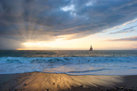 A Beautiful Sunset With a Boat Sailing along the Ocean Water As Sun Rays Burst Through the Clouds