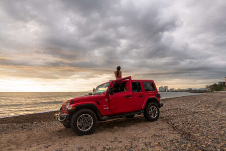 PuertoVallarta, Jalisco, Mexico - 07 \ 27 \ 20 : The 2019 Jeep Wrangler Unlimited Sahara off-road with the ocean and cityscape in the background