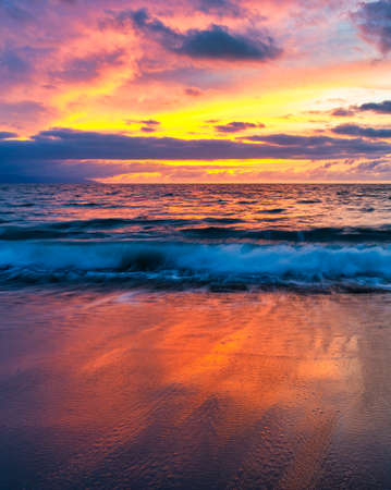 A Colorful Ocean Sunset Sky as a Gentle Wave Rolls to Shore Archivio Fotografico