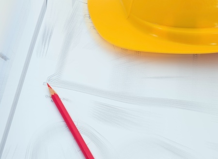 Construction plan with yellow helmet and red pencil photo