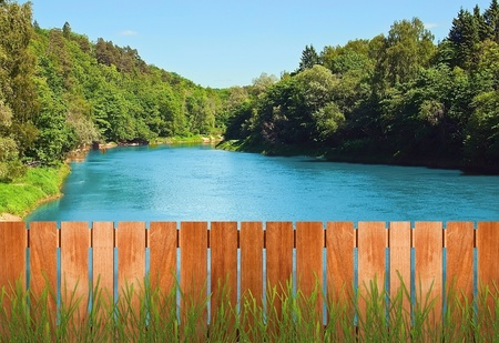 View over fence to the river in forest on sunny summer day photo