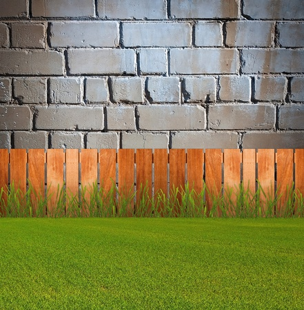 Green grass in garden with fence near the brick wall Stock Photo - 10954842