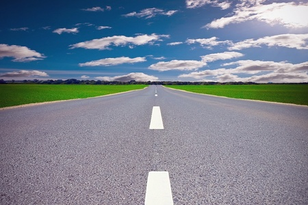 open country: Asphalt road in field on cloudy day