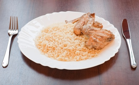 Rice with chicken on plate over wooden table photo