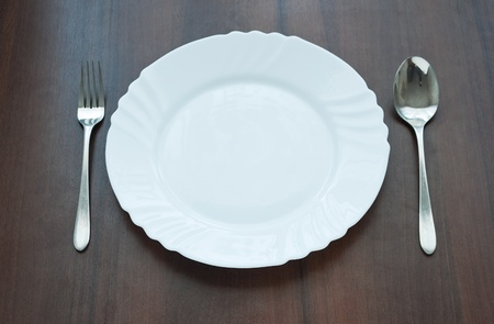 Plate with fork and spoon on wooden table photo