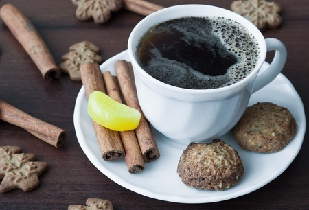 Coffee with cookies and cinnamon stick on wooden background photo
