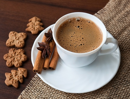 Coffee cup on sacking material with cinnamon stick and cookies photo