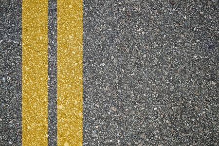 Pattern of asphalt texture with twoyellow lines photo